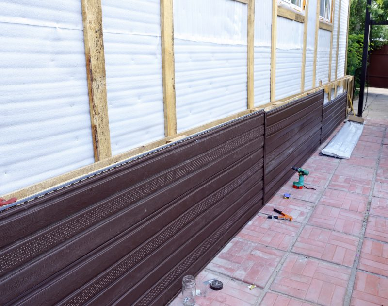 Installation of brown plastic siding on the facade
